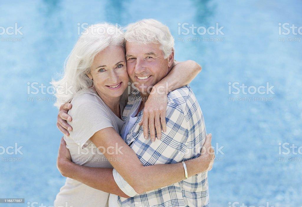 Senior couple hugging poolside royalty-free stock photo