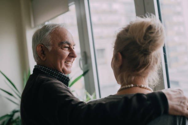 Senior couple hugging while looking through the window in a living room stock photo