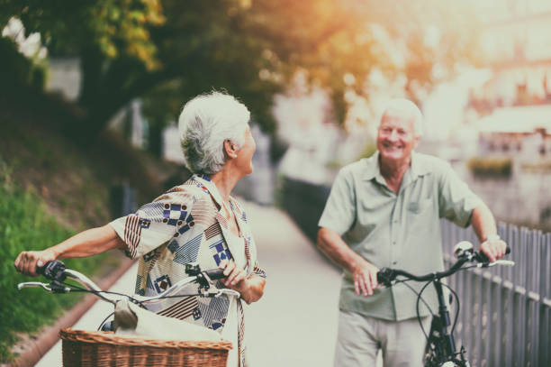 Senior couple in a city Ljubljana Cheerful senior couple walking with bikes in Ljubljana, Slovenia, Europe. ljubljanica river stock pictures, royalty-free photos & images