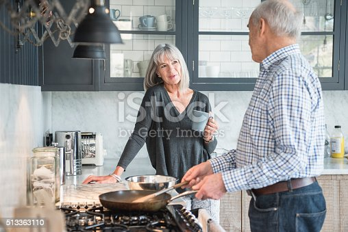 istock Senior couple in a kitchen making dinner and talking 513363110