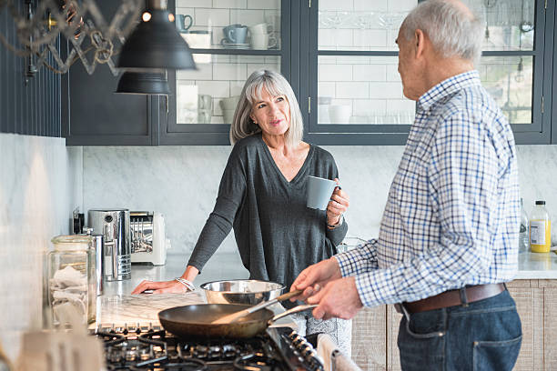 Senior couple in a kitchen making dinner and talking Senior man making a meal on the hob talking to his wife, she is holding a cup of coffee and smiling. The man is using a frying pan on the stove. 60 64 years stock pictures, royalty-free photos & images