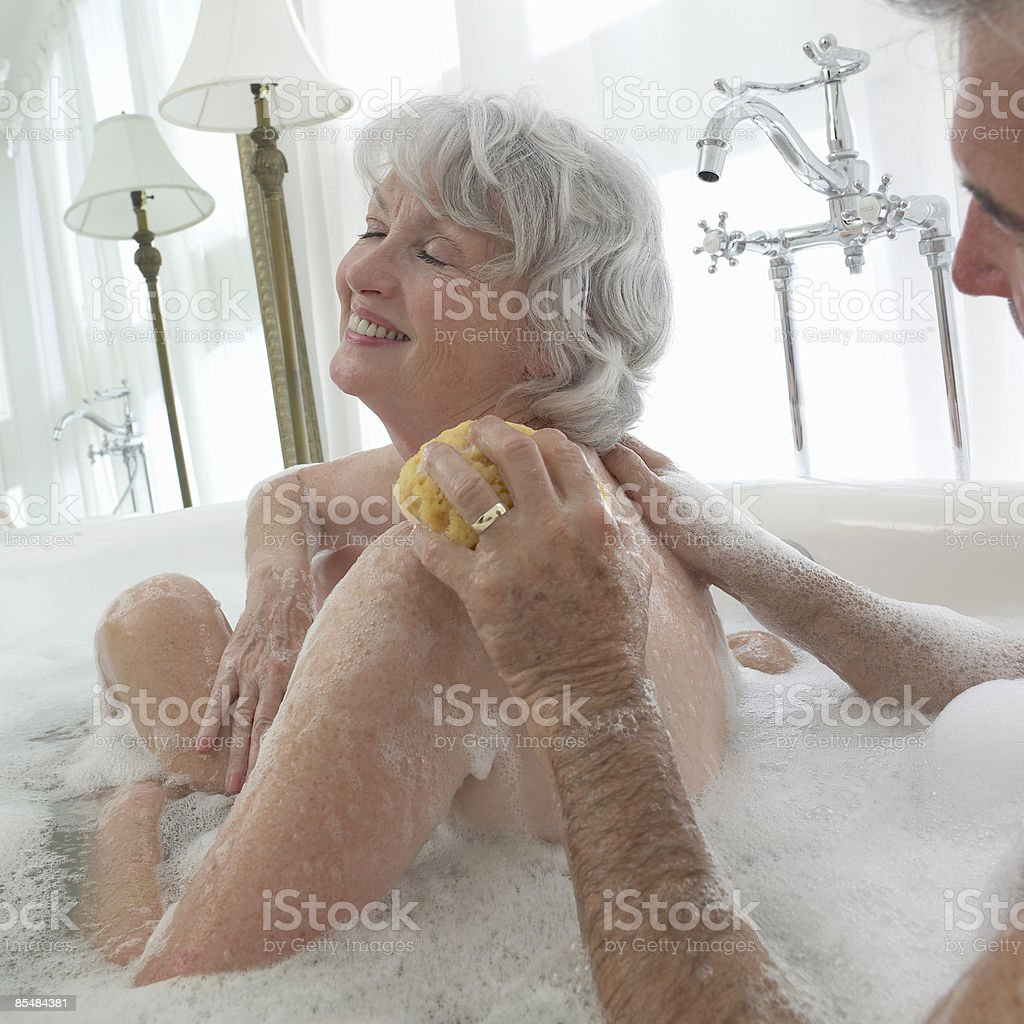 Senior couple in bath together washing women back royalty-free stock photo