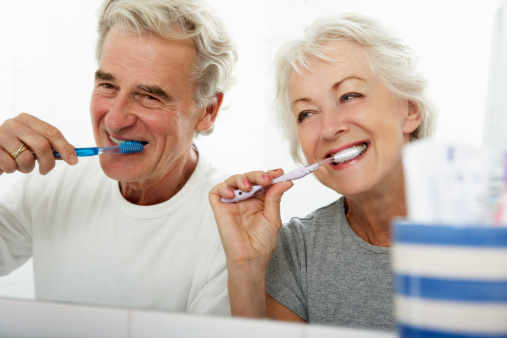 istock Senior Couple In Bathroom Brushing Teeth 171329809