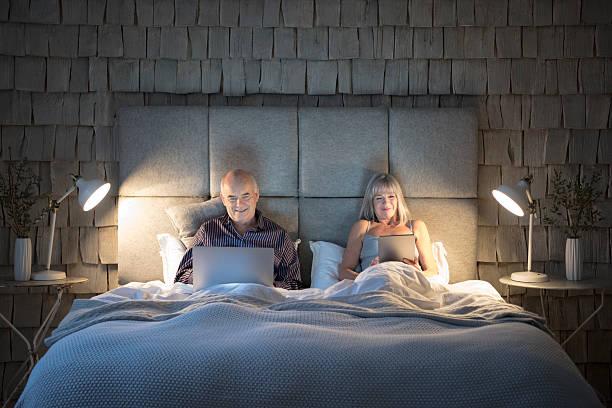 altes paar im bett bei nacht mit laptop und tablet-pcs - nachttischleuchte stock-fotos und bilder