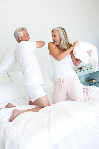 altes paar im schlafzimmer mit pillow fight - kissenschlacht paar stock-fotos und bilder