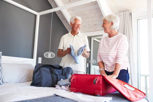 älteres paar im schlafzimmer verpackung koffer für urlaub - 70 jahre kleidung stock-fotos und bilder