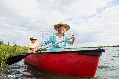 istock Senior couple in canoe on water 472189395