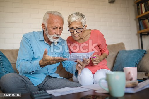 istock Senior couple in debt calculating bills at home 1098410186
