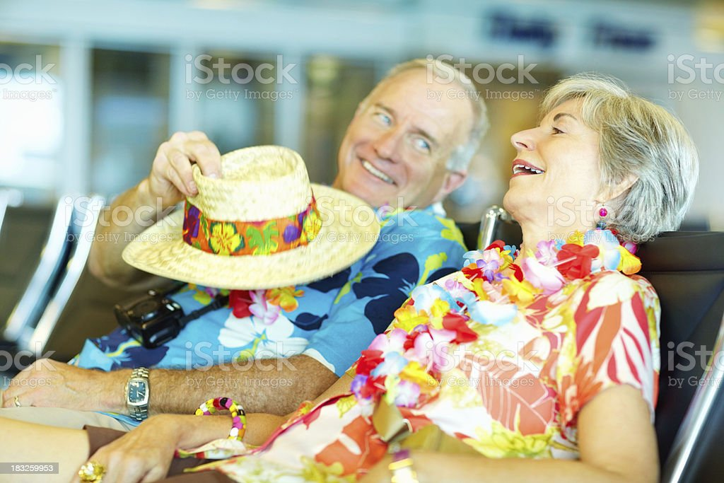Senior couple in floral clothing waiting at an airport lounge royalty-free stock photo
