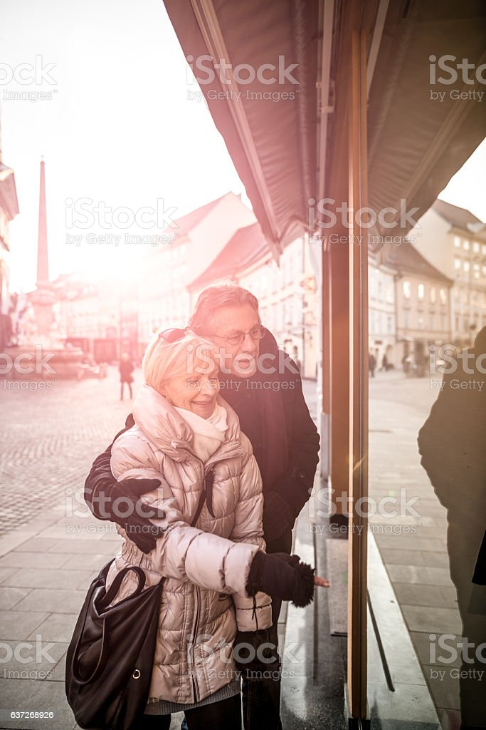Senior couple in front of a shop window stock photo