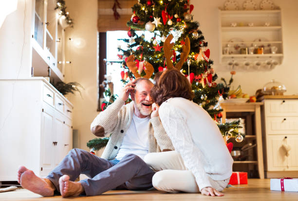 senior couple in front of christmas tree wearing deer antlers. - old man feet stock photos and pictures