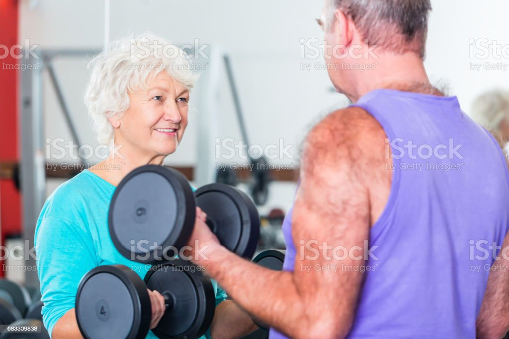 Senior couple in gym lifting dumbbell foto stock royalty-free