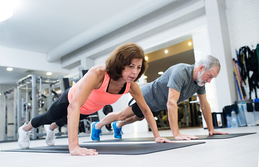 istock Senior couple in gym working out, doing push ups 644362084