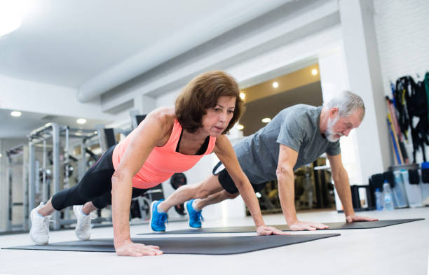Senior couple in gym working out, doing push ups stock photo