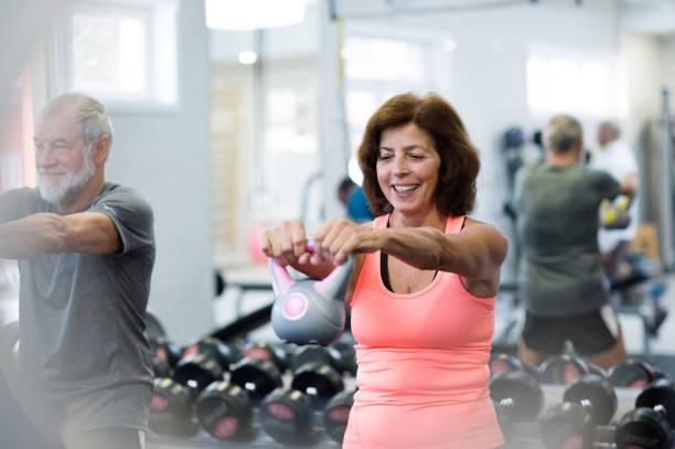 pareja de la tercera edad en el gimnasio haciendo ejercicio usando timbres. - pesa rusa fotografías e imágenes de stock