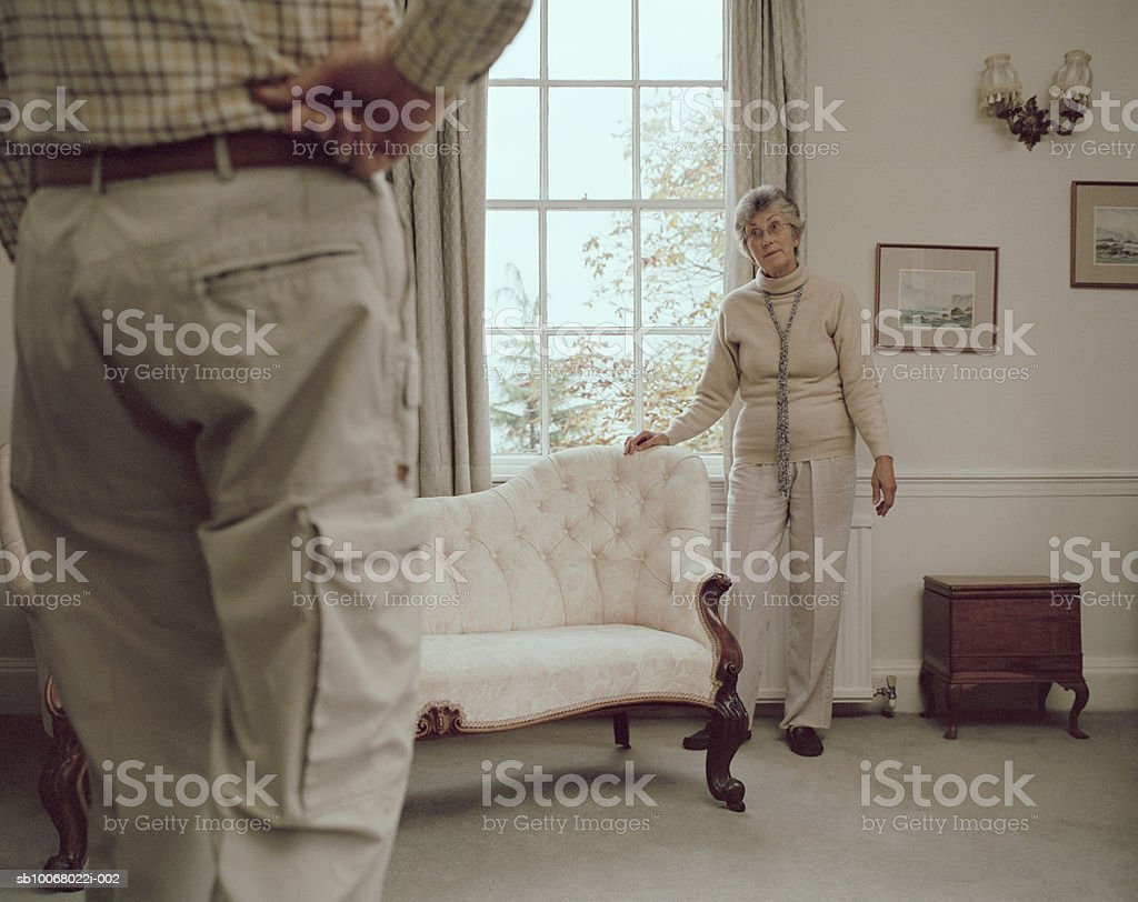 Senior couple in living room, woman standing by sofa royalty-free 스톡 사진