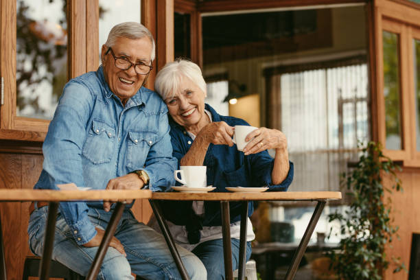 Senior couple in love at coffee shop Senior couple in love at coffee shop. Beautiful portrait of old man and woman sitting at cafe table with coffee looking at camera. active seniors stock pictures, royalty-free photos & images