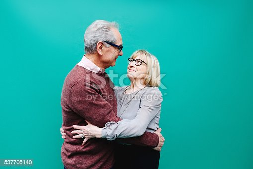 Vintage toned image of a senior couple looking happy against a vibrant turquoise background. Positive emotion, technology, progress, young at heart concepts.