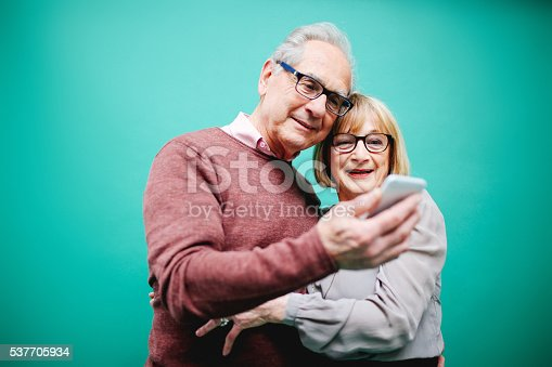 Vintage toned image of a senior couple looking happy against a vibrant turquoise background, looking at the smartphone. Positive emotion, technology, progress, young at heart concepts.