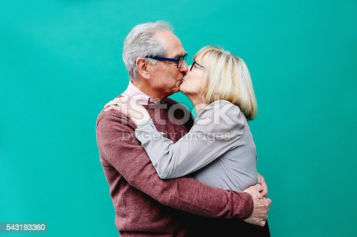 Vintage toned image of a senior couple, kissing, looking happy against a vibrant turquoise background. Positive emotion, love, young at heart concepts.