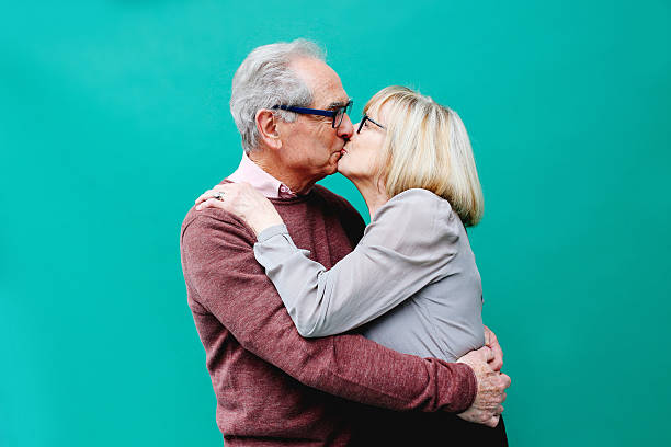Senior couple in love Vintage toned image of a senior couple, kissing, looking happy against a vibrant turquoise background. Positive emotion, love, young at heart concepts. love at first sight stock pictures, royalty-free photos & images