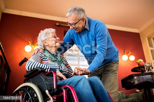 Senior couple in love, senior man take care of his wife in wheelchair