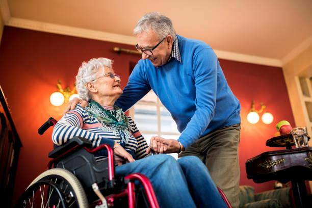 Senior couple in love, senior man take care of his wife stock photo