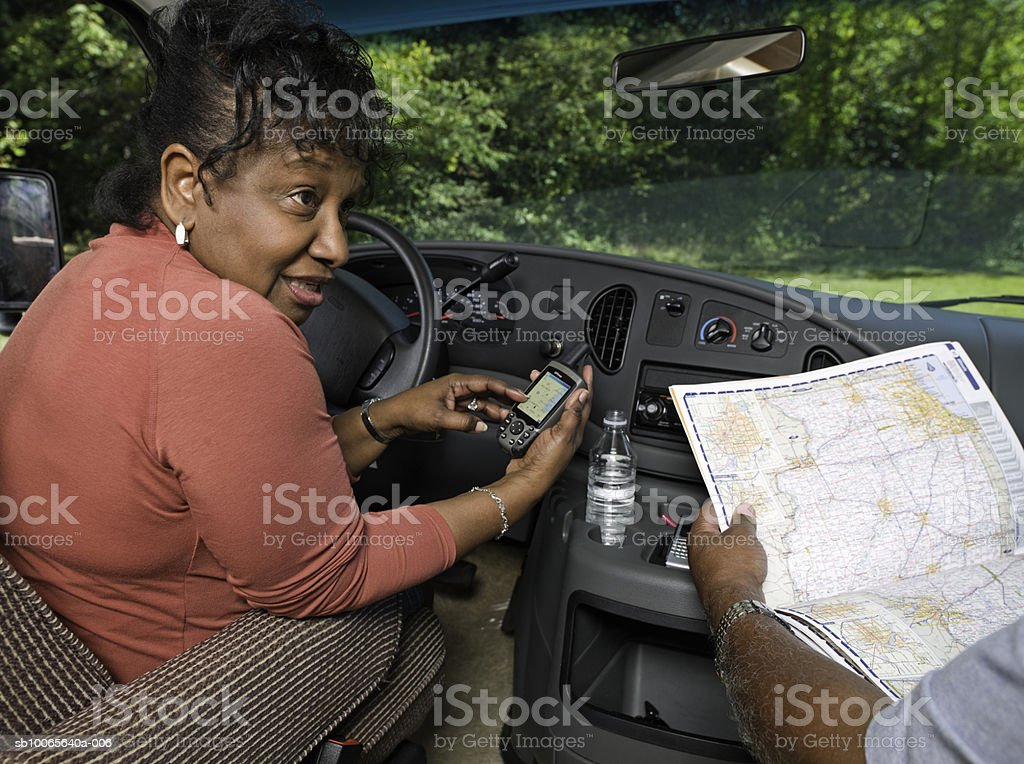 Senior couple in motorhome, man with map and woman with satellite navigator royalty-free stock photo