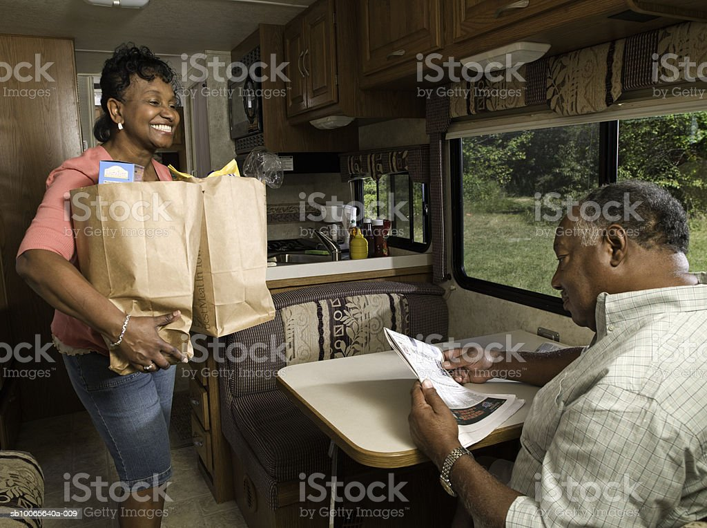 Senior couple in motorhome, woman holding grocery bag foto de stock royalty-free