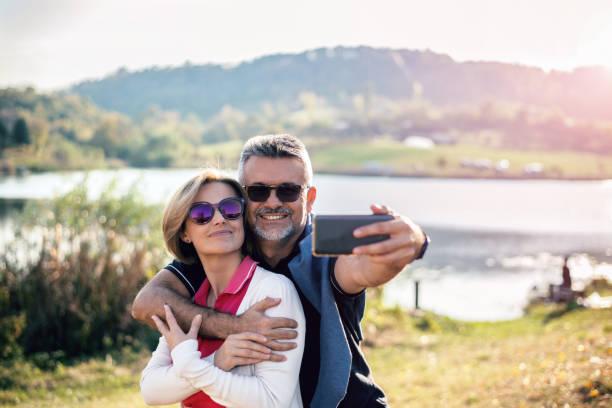 älteres paar in der natur fotografieren mit smartphone - senior bilder wasser stock-fotos und bilder