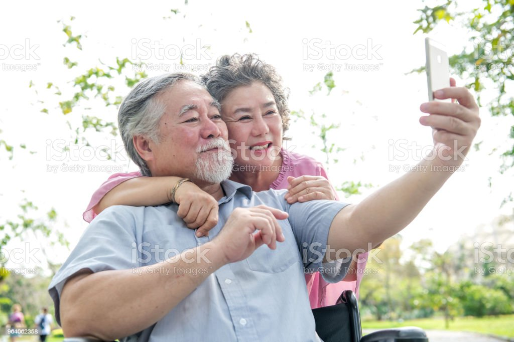 Senior couple in park portrait. Chinese old couple in park, relaxing, smiling, taking selfie. Medium shot. - Royalty-free Active Seniors Stock Photo