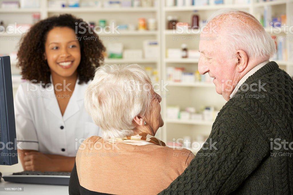 Senior couple in pharmacy with pharmacist royalty-free stock photo
