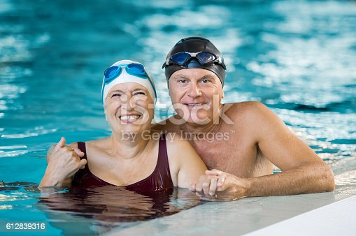 612839448istockphoto Senior couple in pool 612839316