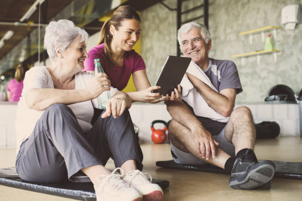 Couple de personnes âgées en centre de réadaptation. Entraîneur personnel montrant quelque chose sur la tablette numérique. - Photo