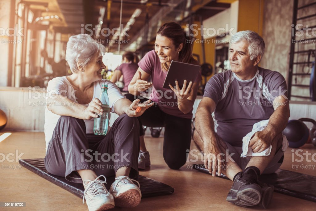 Senior couple in rehabilitation center. Personal trainer showing something on digital tablet. stock photo