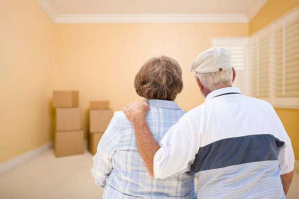 Senior Couple In Room Looking at Moving Boxes on Floor Hugging Senior Couple In Room Looking at Moving Boxes on the Floor. buy single word stock pictures, royalty-free photos & images