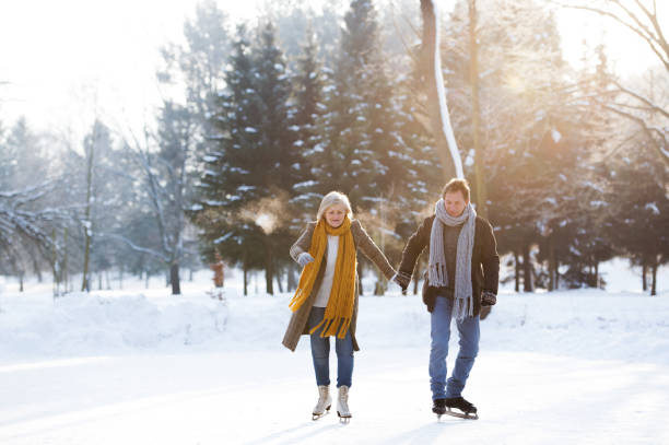 Senior couple in sunny winter nature ice skating. Beautiful senior woman and man in sunny winter nature ice skating. ice skating stock pictures, royalty-free photos & images