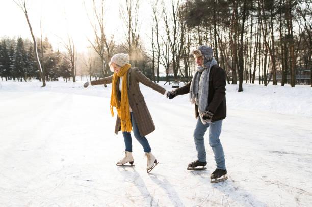 senior couple in sunny winter nature ice skating. - wintermantel damen wolle stock-fotos und bilder