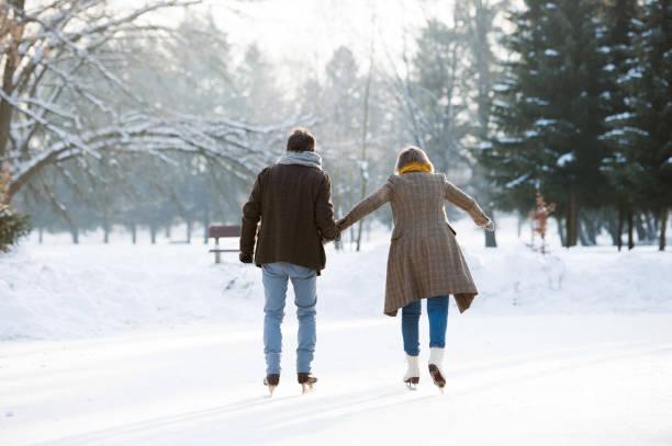 senior couple in sunny winter nature ice skating, rear view. - wintermantel damen wolle stock-fotos und bilder