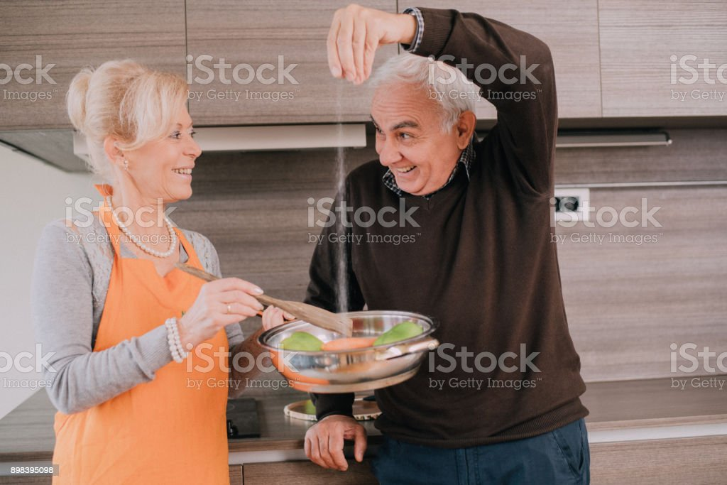 Senior couple in the kitchen cooking dinner, the man is adding the salt stock photo