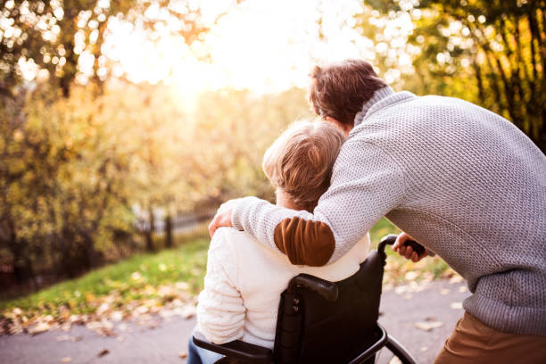 Senior couple in wheelchair in autumn nature picture id875265552?b=1&k=6&m=875265552&s=612x612&w=0&h=mavb0yha7tlyyjgl6hwnvlxp9te83stvrvza4td4bn4=