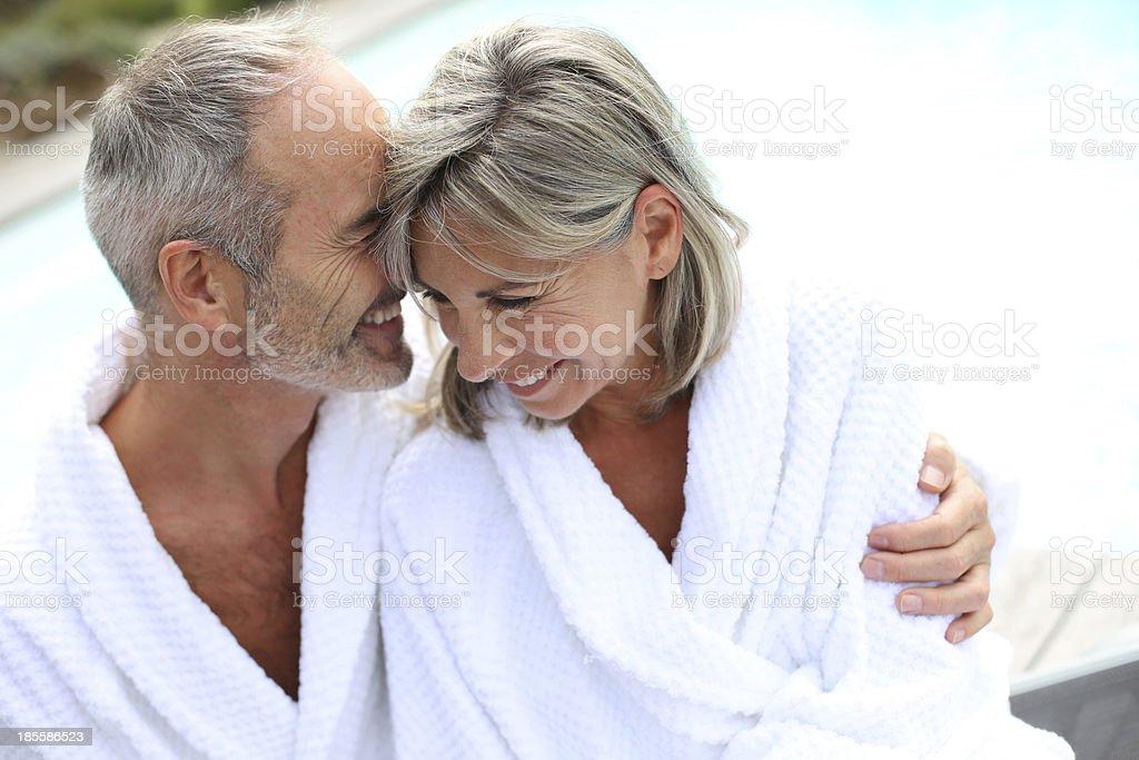 Senior couple in white bathrobe embracing each other stock photo