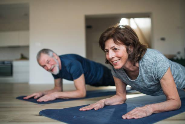 Ein leitendes Ehepaar drinnen zu Hause, das Übung auf dem Boden macht. – Foto