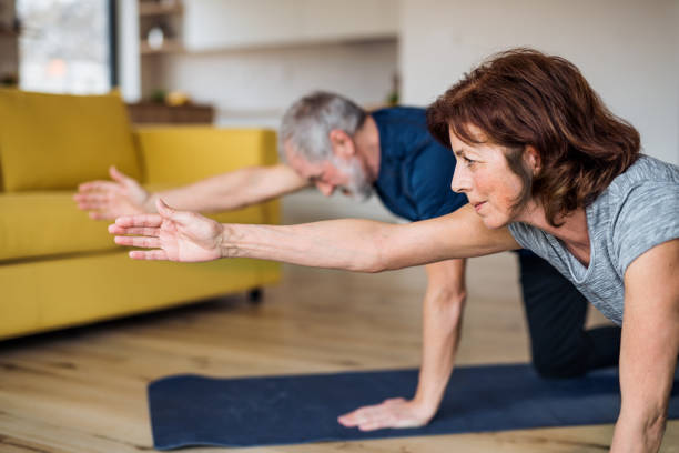 A senior couple indoors at home, doing exercise on the floor. A happy senior couple indoors at home, doing exercise on the floor. exercising stock pictures, royalty-free photos & images