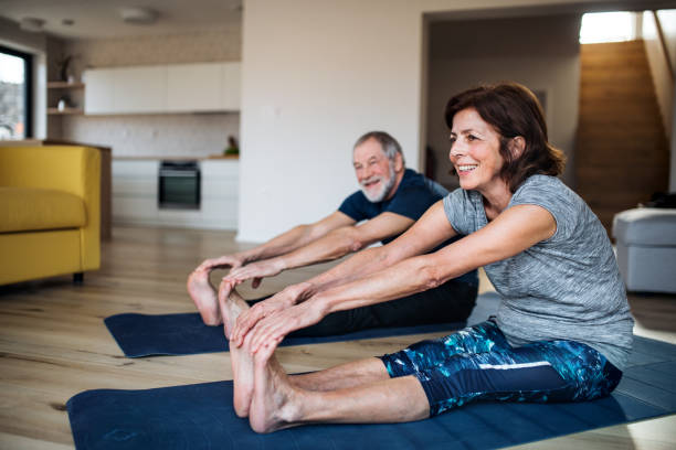A senior couple indoors at home, doing exercise on the floor. stock photo