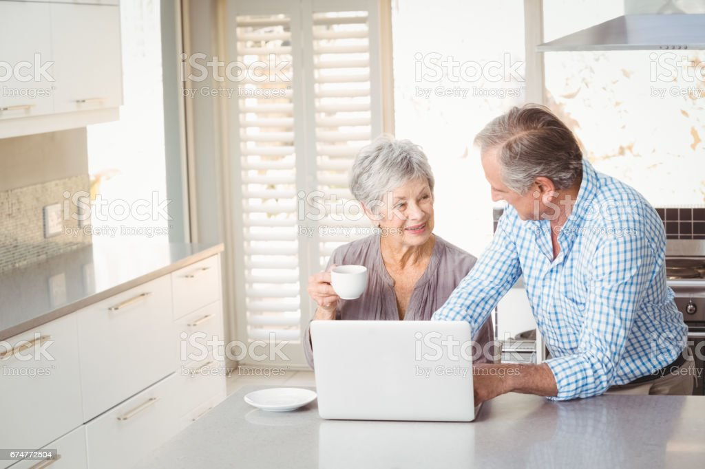 Senior couple interacting in kitchen stock photo