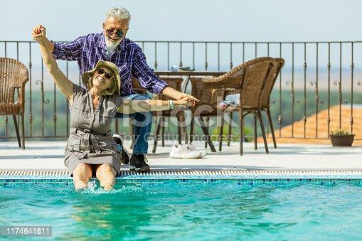 Senior couple hugging poolside