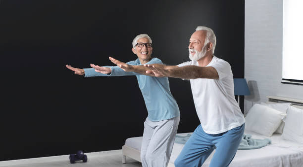 Senior couple is doing fitness training at home.  Healthy lifestyle concept. stock photo