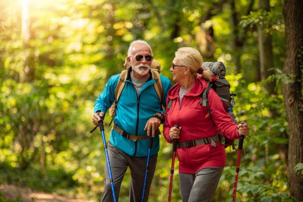 Senior couple is hiking in forest.Adventure, travel,hike and people concept stock photo