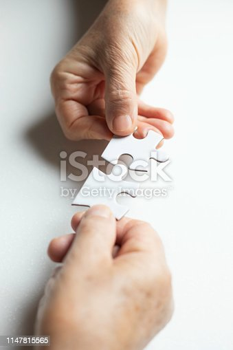 istock Senior Couple is Playing Puzzle. 1147815565